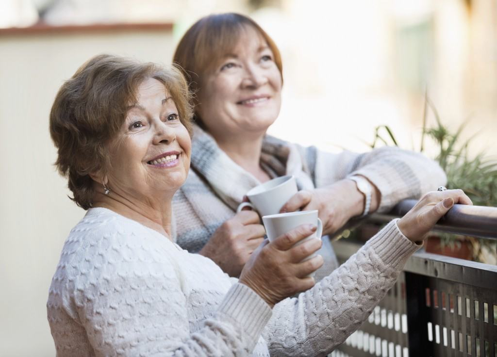 Portrait of positive happy female pensioners drinking tea and smiling on balcony