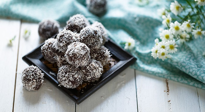 Cocoa and coconut energy balls on white background