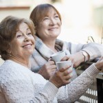 Portrait of positive happy female pensioners drinking tea